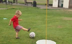 A young boy kicks a ball into a hole